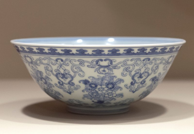 Bowl, porcelain, light blue underglaze, Ching Dynasty, Yung Cheng period (1723-35). On exterior flowering plants and garlanded scrolls. Floral spray with surrounding bands of stylized floral motifs inside. Six character Yung Cheng mark within double circle on base.