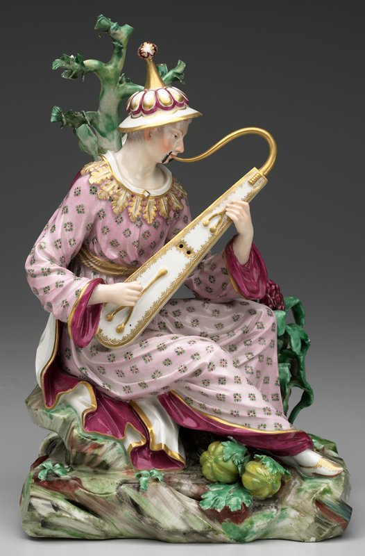 male figure seated before trees playing instruments; wearing conical hats and puce flowered robe on rockwork base with melons; blue crowned interlaced C's