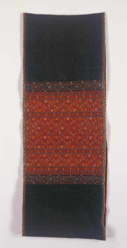 indigo dyed fabric edges in beads and very small pompons, sewn into a wide tube; embroidered section at center with geometric design in rust, white, blue, green and orange