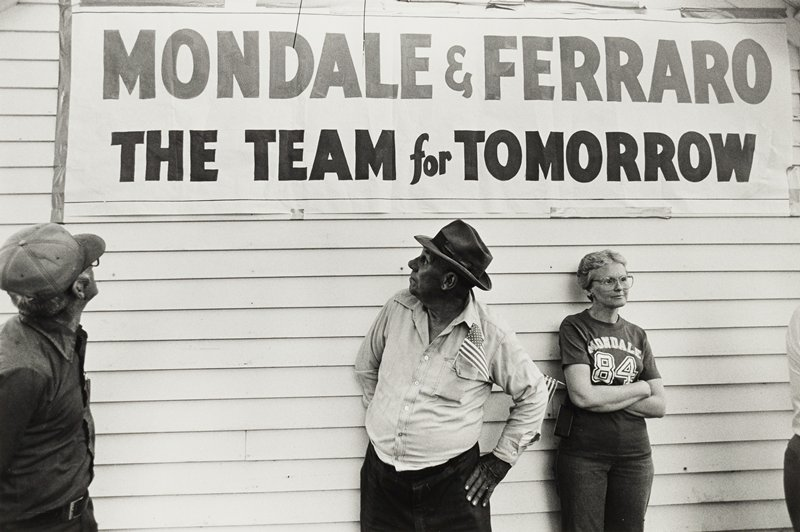 Two men looking at banner 'Mondale & Ferraro The Team for Tomorrow' with woman wearing 'Mondale 84' t-shirt