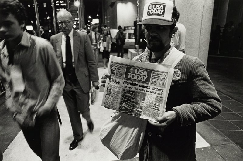 Man center right holding USA Today newspaper