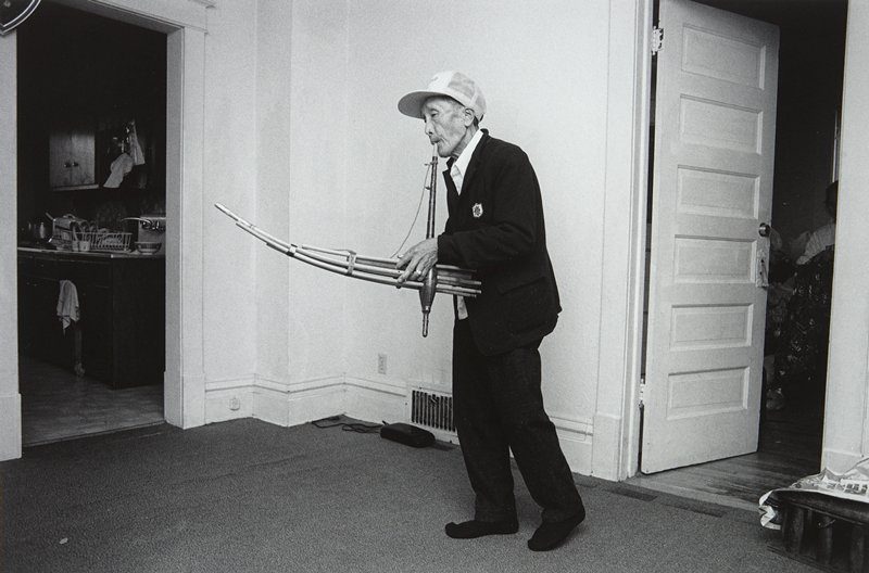 black and white photo of man in cap playing wind instrument; kitchen visible on left