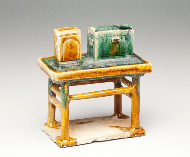 Tomb furniture; table with one horizontal support on each long side and two horizontal supports on each short side resting on a base; 2 rectangular boxes, one glazed tan and the other glazed green, on the table