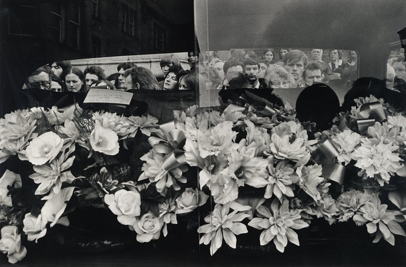 casket covered in flowers, foreground; funeral goers viewed through the hearse rear window, background
