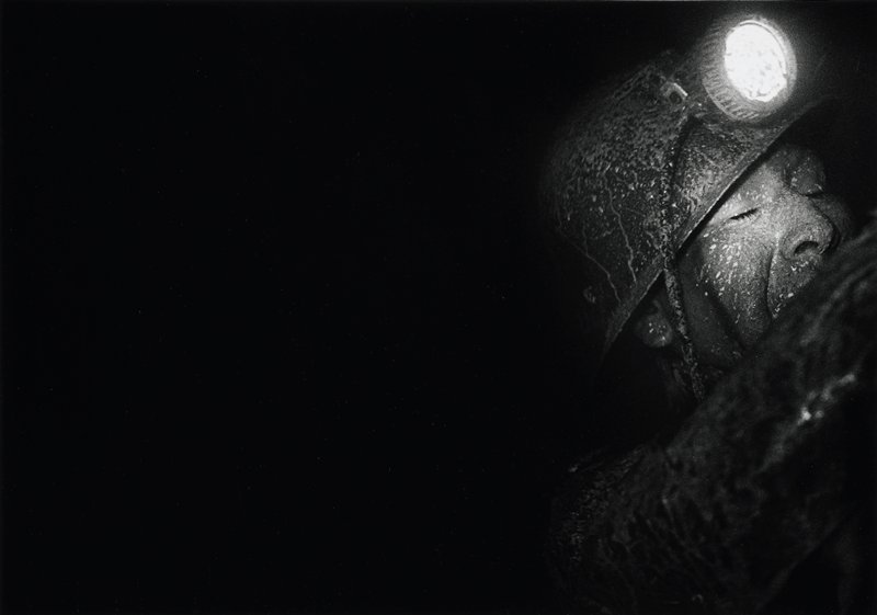 black with image of miner's head, URC; face is covered in grime and the eyes are closed