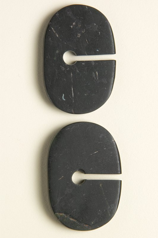 2 oval-shaped discs with flat sides; slightly wider at bottom; dark black/green stone with thin brown streaks