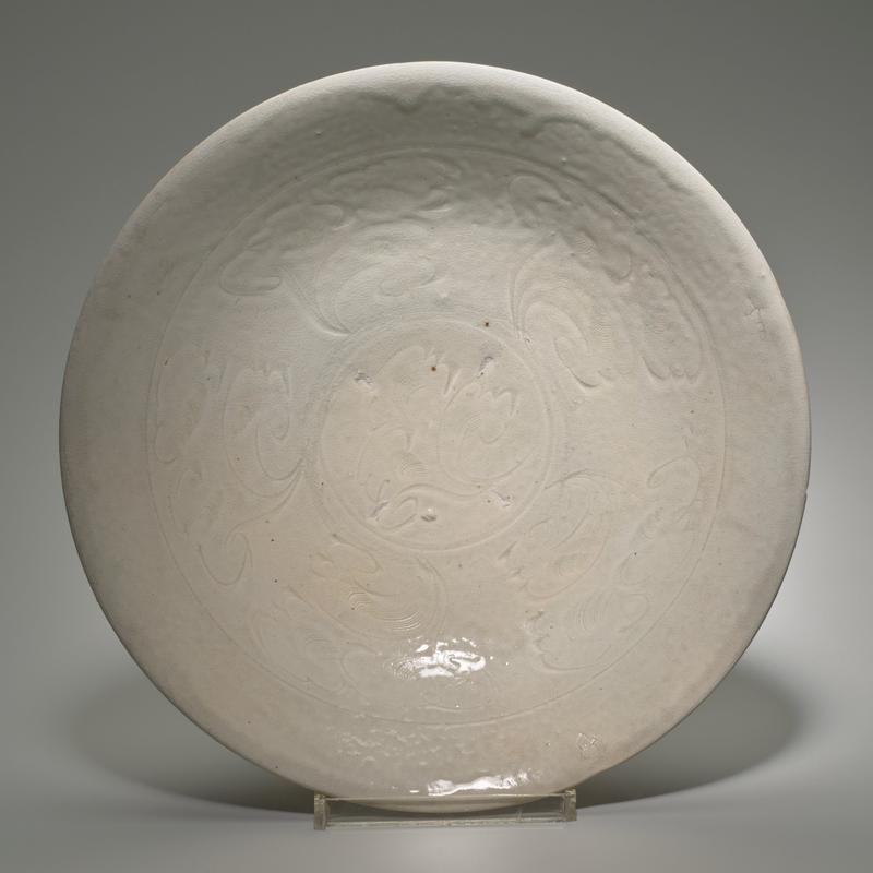 shallow bowl on short foot ring; whitish-blue glaze; decorated with incised and combed scrolls on interior