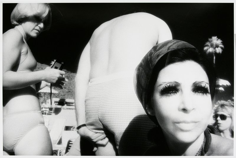 close-up of smiling woman's face at R, wearing false eyelashes; man at center, seen from back, slightly bent over, wearing swim trunks and scratching the back of his PL leg; blonde woman wearing a bikini and holding a camera at L; another woman's face at LRC; matted