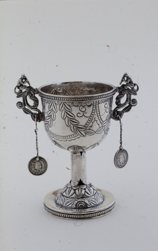 Cup on stem, silver, Peruvian XXc (?) cat. card dims H 4-3/4 x diam 3'. Cup has two handles, pendant Peruvian coins.