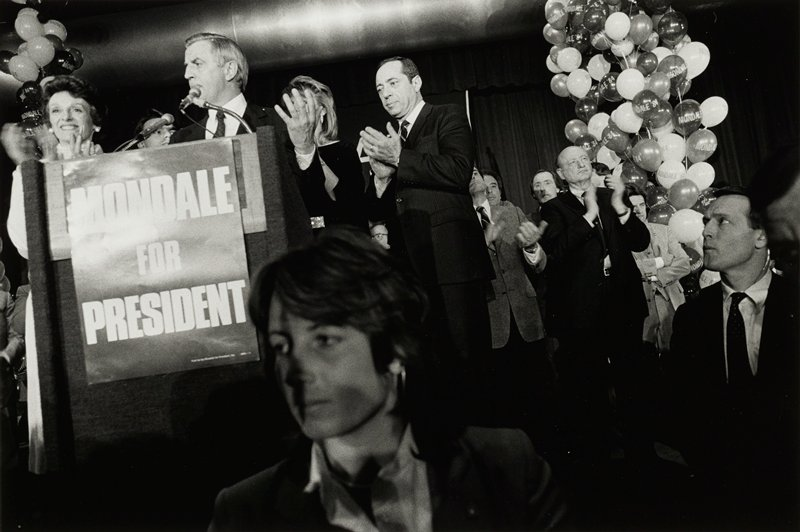 Walter Mondale, left, behind podium, Mario Cuomo clapping, center, woman's face, lower front center