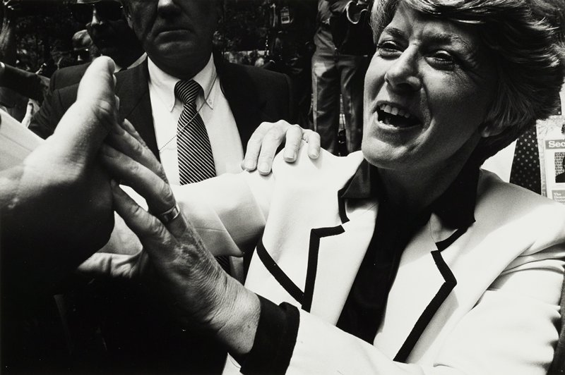 Geraldine Ferraro, facing left, reaching to touch a hand; man with striped tie in background