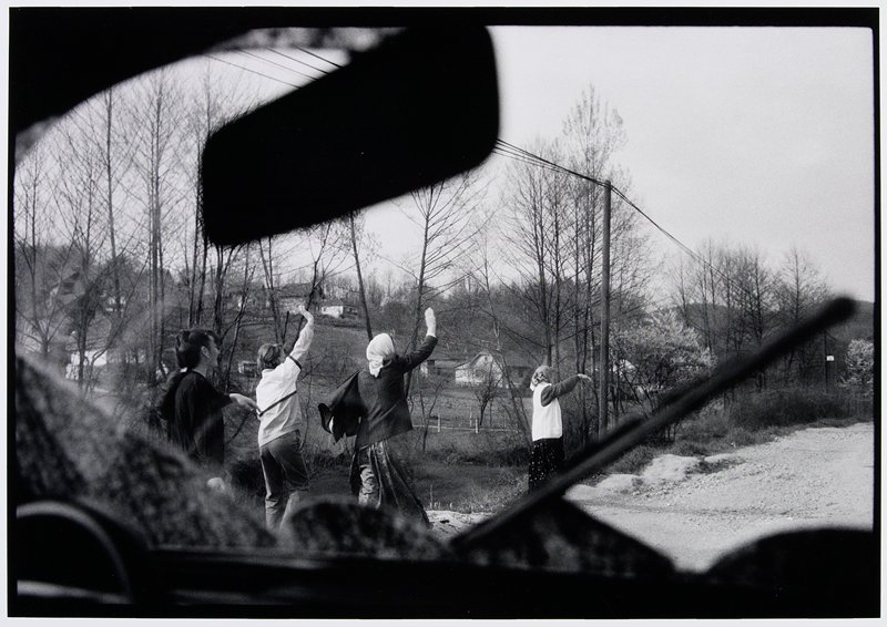 woman waving down a road seen from an automobile