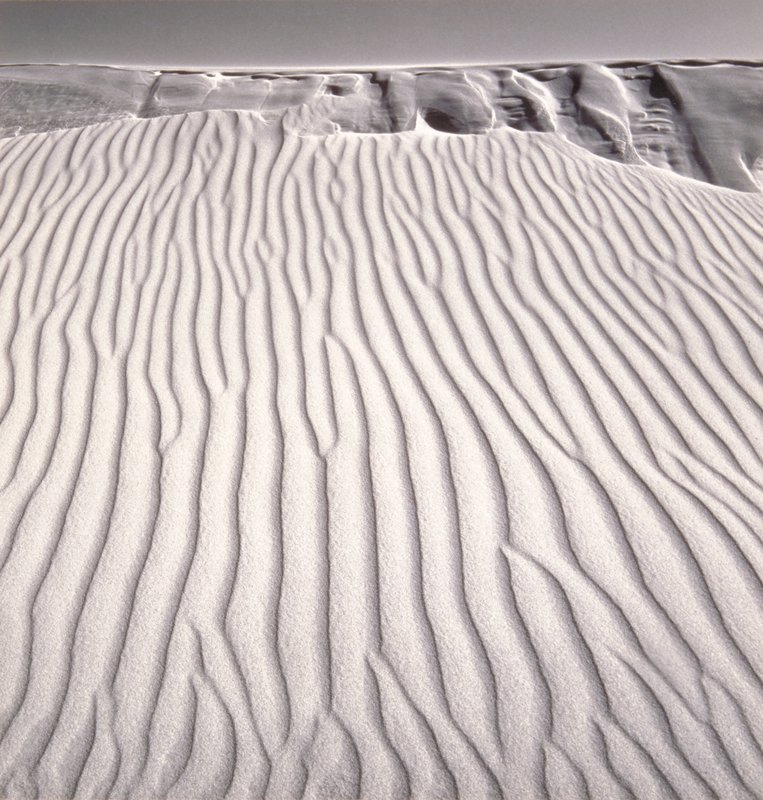 sculpted lines in sand leading to dropoff and dunes in background