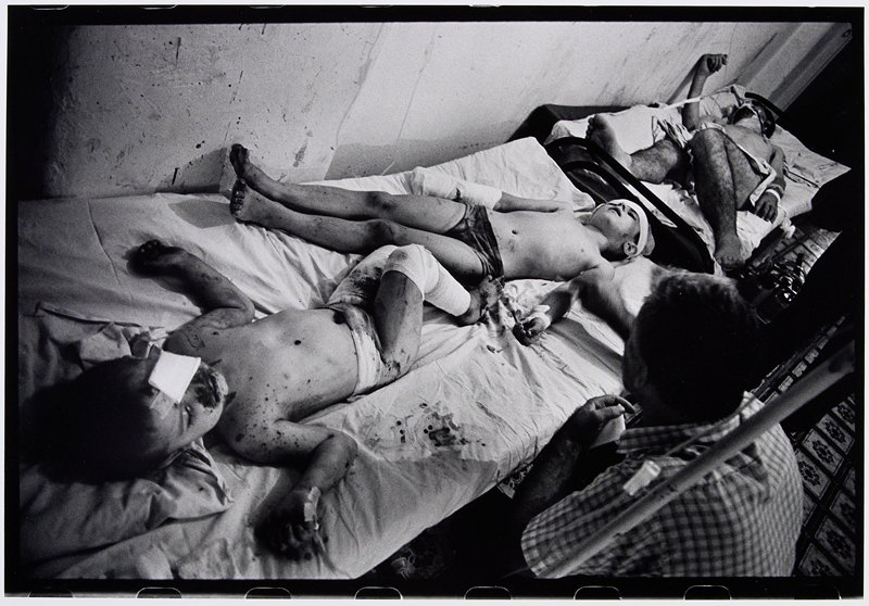 two wounded boys with bandaged arms, legs and head lying in bed