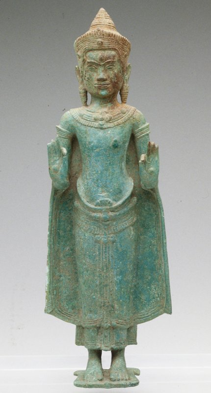 Khmer Style; figure of Buddha standing on a lotus petal; both hands are raised; figure adorned with a diadem, long earrings, a necklace and armlets