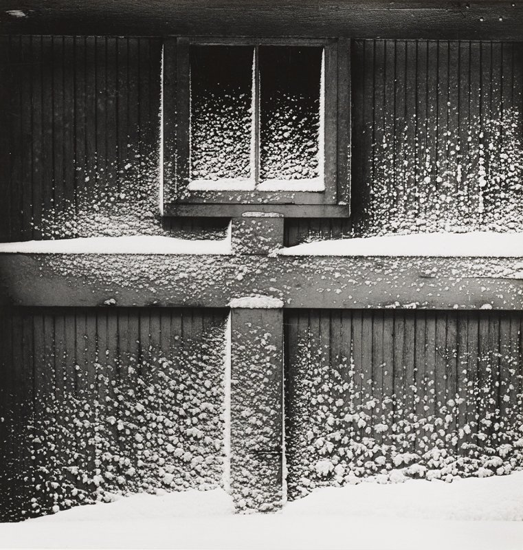 clumps of snow sticking to vertical siding on wall and window