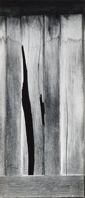 vertical wooden boards with tide marks, cracks and two losses; horizontal board at bottom