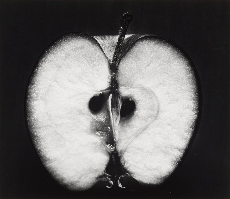 half of an apple, with two seeds and stem