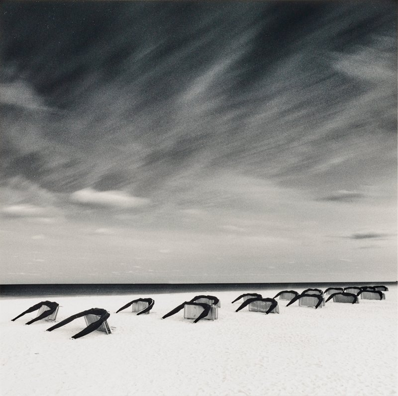 flat sandy beach with water at horizon line; two rows of beach lounge chairs on their sides with U-shaped black umbrella (?) leaning on top of each chair; striated clouds in sky