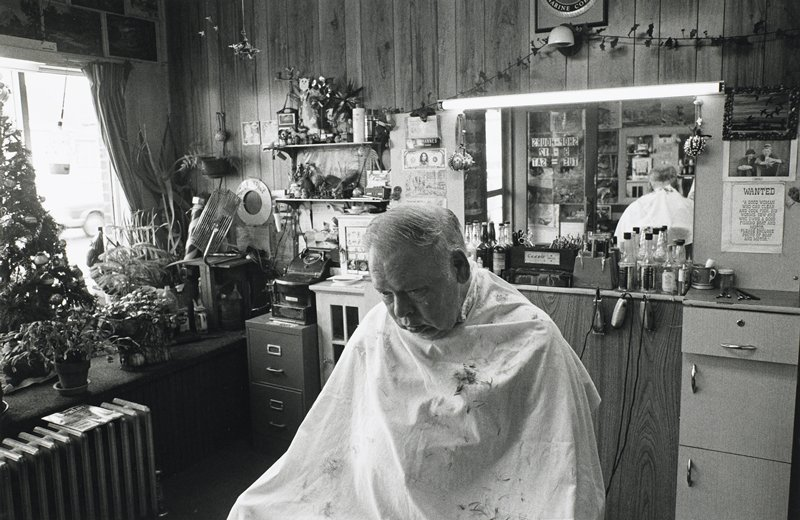 black and white photo of man in barbershop, head down