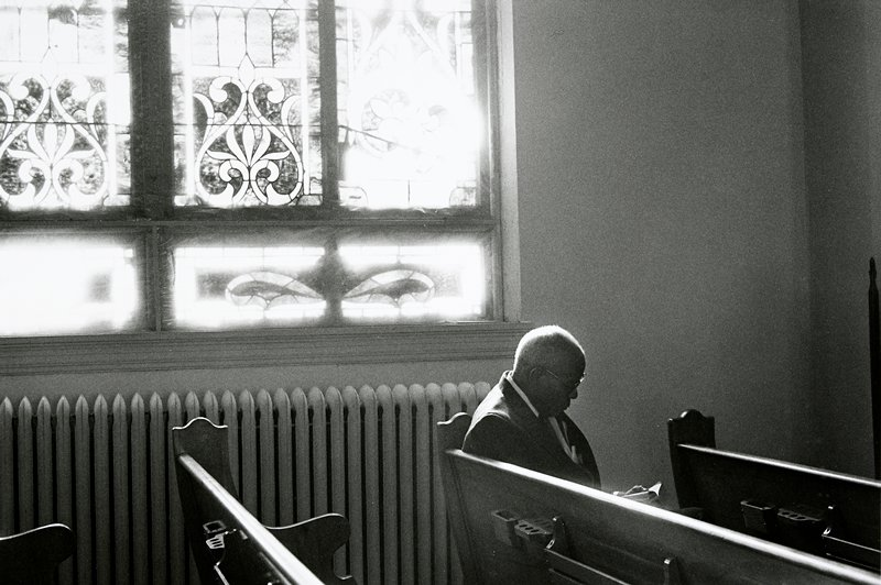 black and white photo of man in church pew, reading