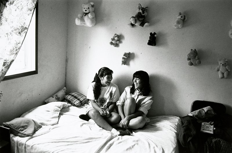 black and white photo of two girls seated on bed; stuffed animals on wall