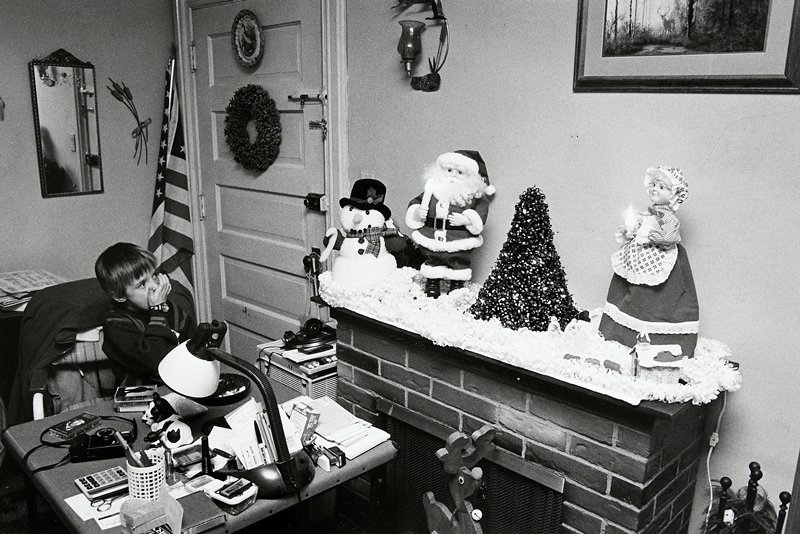 black and white photo of boy looking at mantle with Christmas decorations including Mr. and Mrs. Claus