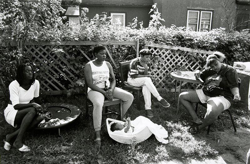 black and white photo of four women in background, baby in rocker