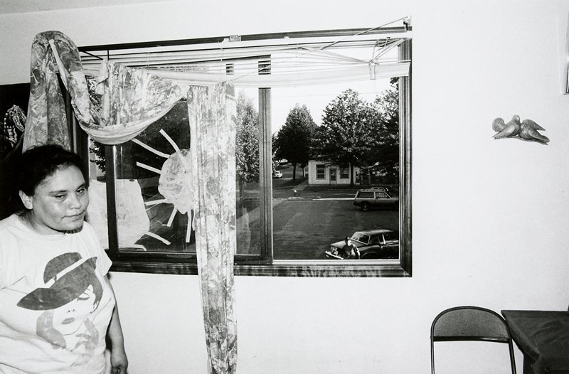 black and white photo of woman in front of taped window