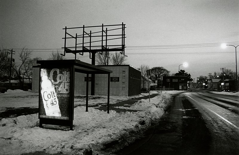 black and white photo of bus stop with 'Colt 45' advertisement