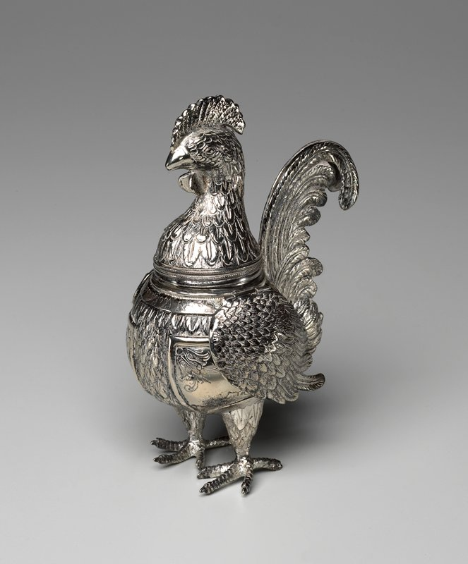 standing rooster with hinged wings; head removes to reveal 2nd lid, pierced with holes and topped with a small chicken