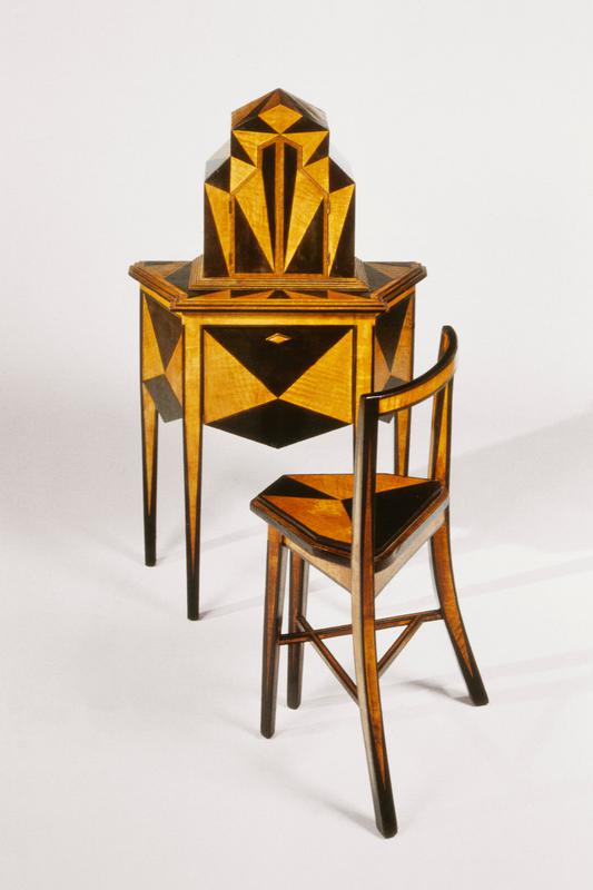 Box with two doors sits on top of table, black triangles of various sizes throughout