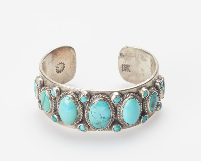 Hopi, silver sheet band, set with 7 large graduated elliptical turquoises interspersed; twisted wire and stamped decoration; 12 small stones cat.200, J#238