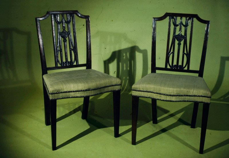 side chair, one of a pair; Sheraton type; open garland and urn back; striped pink and green silk brocaded seat, with serpentine front edged with double row of brass nail heads; front legs square and slightly tapered; back legs square and curved back slightly