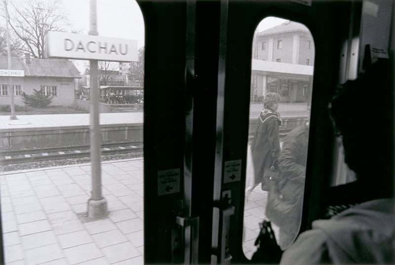 looking out train window at sign for Dachau