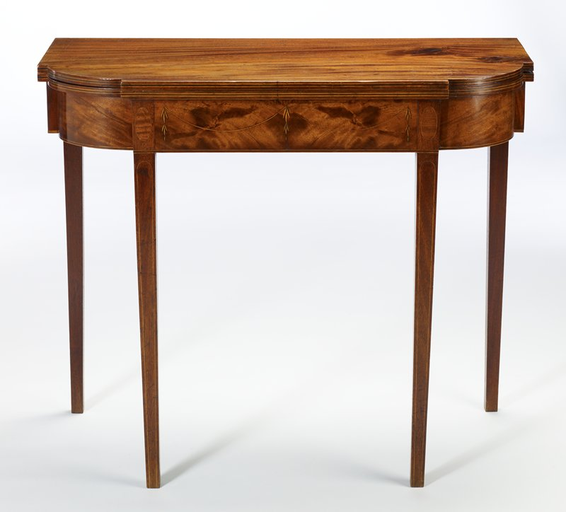 card Table, folding, hinged top; Hepplewhite design; corners of top cut in recessed quarter-round design popular during the last ten years of the century; narrow inlay of holly forms panels on legs; in center of skirting are inlaid two swags from which hang pendant husks; above the legs are oval inlaid panels formed with the same wood