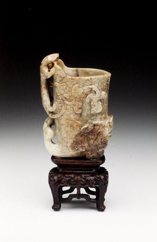 Carved with a dragon's head at the base, with another dragon climbing at the side to form the handle, the grey-green stone with brown andblack markings, crudely carved with archaistic scrollwork. Flaw chip at rim. Weatherd at one side more greatly than the other. Former Classification: Jade