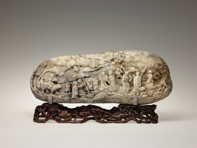 Of loaf shape, carved in high relief with buddhist divinities and demons on both sides amidst clouds and wave motifs and a traditional heavenly mountainscape. Broken in two pieces and repaired. Former Classification: Jade