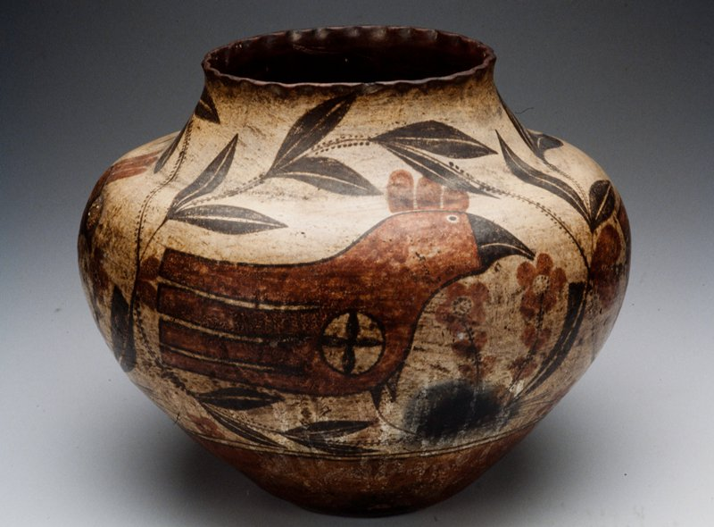Wide bodied vessel with red foot, white ground and black and red details. Three red birds pictured with a plant motif.