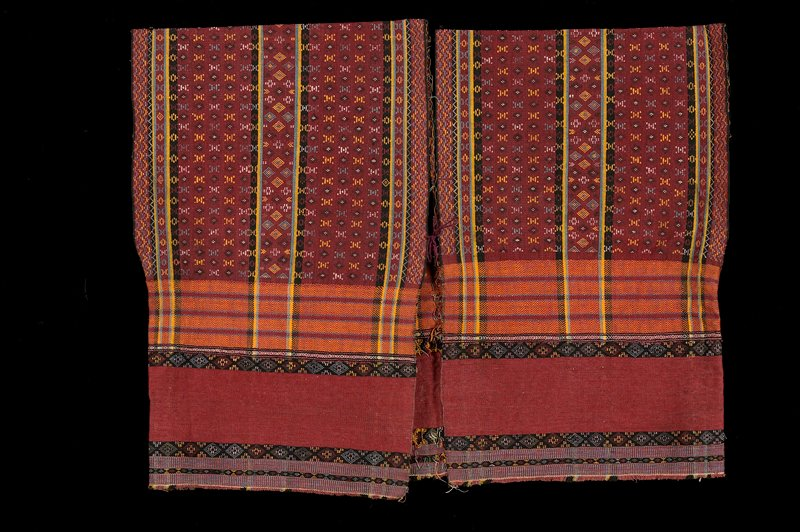 two panels stitched together at center back; woven with decorative pattern and stripes in red, orange, green, yellow, black; cord tie in front