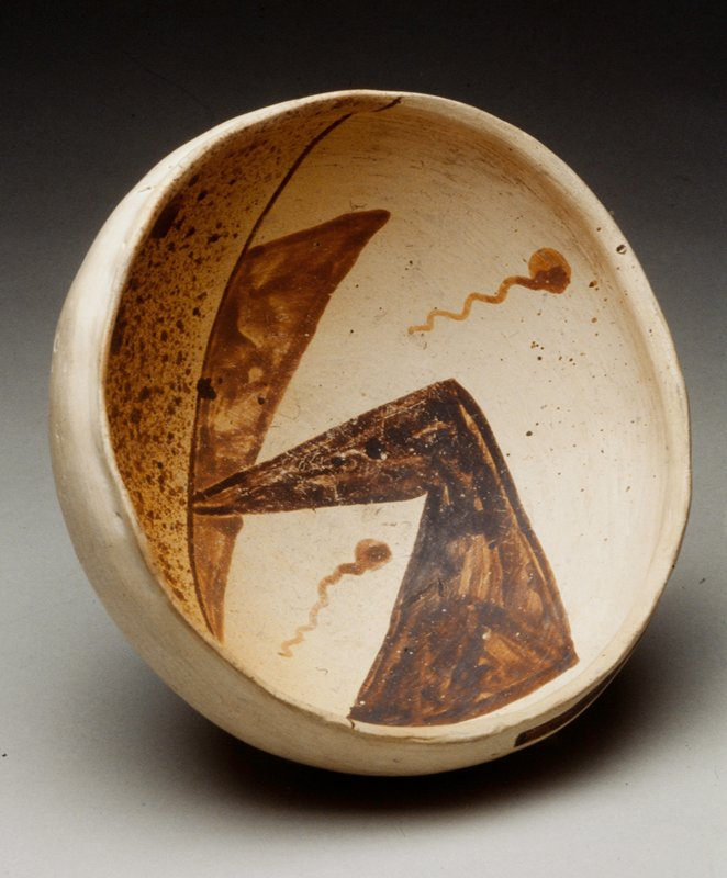 Tan vessel with brown design; one quarter of the vessel is spotted; other area has design with two geometric shapes and two circles with wavy line; exterior has dark brown design near rim on 1/2 opposite spotted area