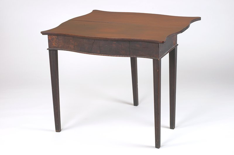 folding card table with detached top and removable drawer; dark finish; tapering legs; curved front; dome-shaped notches on edges of table top