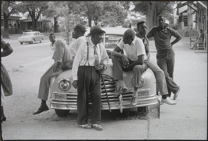 five black men of varying ages sitting on and leaning against a car