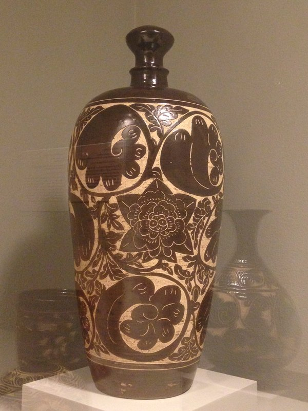 tall vase, slightly flaring outward and inward at shoulder to a garlic head top; brown glaze with floral pattern cut into central band