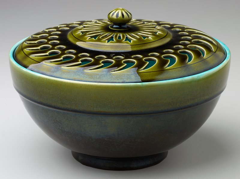 dark green bowl with turquoise interior; dark green cover with central floral openwork design surrounded by openwork circles and teardrop shapes; yellow on bottom of cover