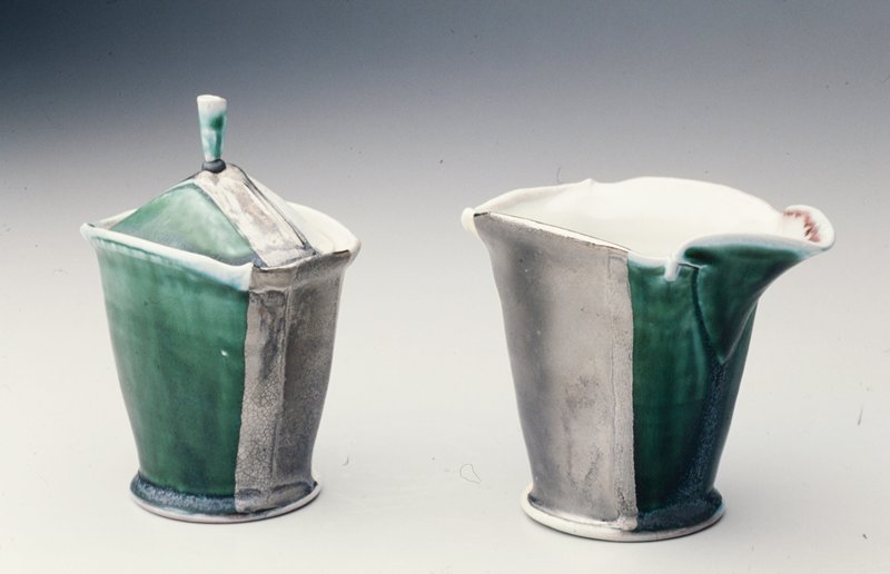 flat circular base; slightly squared-off corners; flaring body; long spout; white interior, green below spout, blue swirls on one side, silver on opposite side, yellow with incised text on back