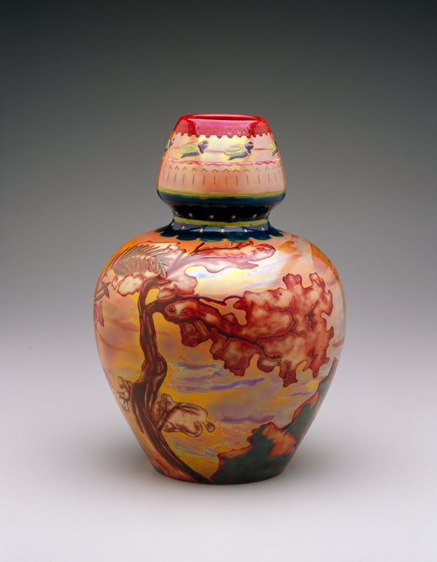 wide shouldered globular vase with extended neck which widens above the base of the neck and tapers slightly to the top; decorated with landscape scene of sumac, other trees and a castle in dramatic polychrome glazes and lustres; earthenware with metallic red Eosin glaze, blue Labrador glaze and other iridescent and matte glazes