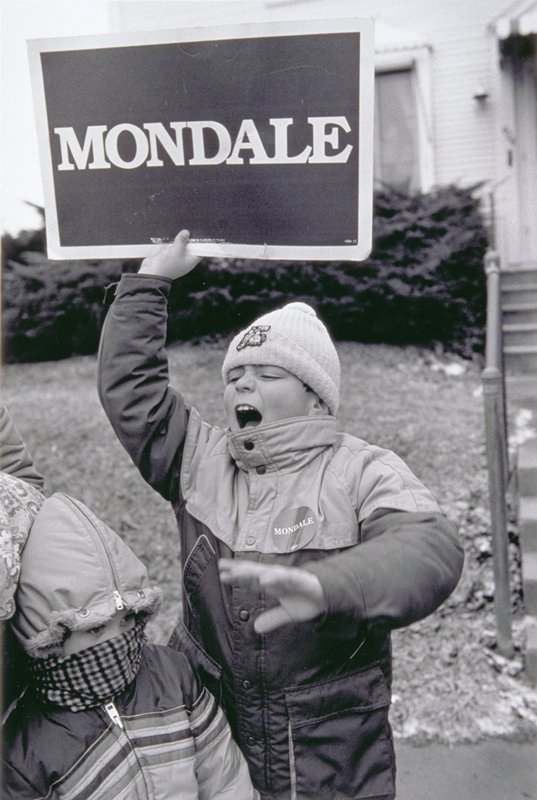 little boy wearing a 'Mondale' button holding a 'Mondale' sign above his head