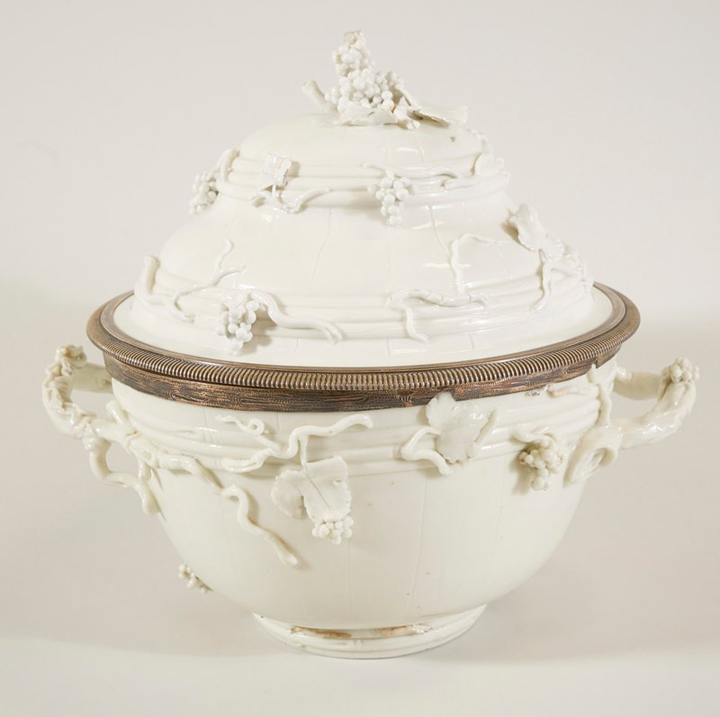 wine bowl and cover,creamy green-white tone typical of capodimonte ware; bowl and cover mounted with chased silver rims; incised with vertical lines, as on mellons; ornamented with leaves, vines and bunches of grapes in high relief; bunch of grapes in the round form finial; Holiday Traditions - Charleston Dining Room - out