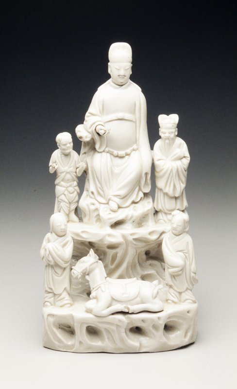 chinese export statuette group blanc-de-chine porcelain, five figures in two tiers on rockwork with large central seated dignitary holding rolled scroll and wearing official hat flanked by small Immortals, one wearing a butterfly hat, the lower tier with two standing children in voluminous robes flanking a recumbent horse; ivory glaze